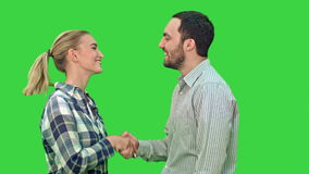 Teen people shaking hands and looking at camera on a Green Screen, Chroma Key. Teen people shaking hands and looking at camera. Close up on a Green Screen stock video