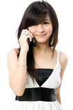 Teen With Phone. An attractive young Asian woman with mobile phone on white background royalty free stock photo