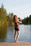 Teen photographer. Teen girl using her phone to take a photograph of a lake Royalty Free Stock Photo