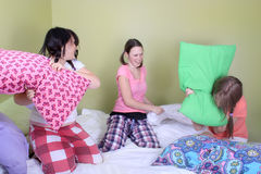 Teen pillow fight. Three teenage girls in their pajamas with pigtails or braids having a pillow fight on a bed at a sleepover stock images