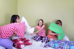 Teen pillow fight. Three teenage girls in their pajamas with pigtails or braids having a pillow fight on a bed at a sleepover royalty free stock image