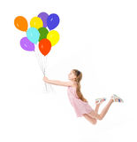 Teen in pink dress flying on balloons. Adorable teen in pink dress flying on bright colorful balloons, long brown hair Stock Images