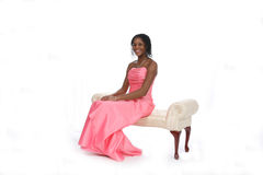Teen in Pink Gown Sitting on Bench. Attractive African American teenage girl wearing a pink strapless gown, sitting on an ivory bench against a white background Stock Images