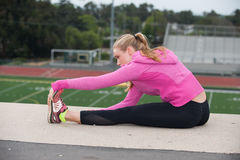 Teen in pink jacket activating muscles over field. Stock Photos