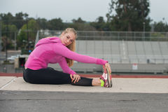 Teen in pink jacket stretching hamstrings over field. Stock Photos