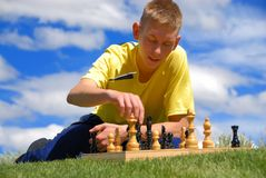Teen play chess. On sunny afternoon day Royalty Free Stock Photography