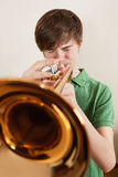 Teen playing gold trumpet. Photo of a young teen playing his gold trumpet Royalty Free Stock Image