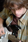 Teen playing guitar. Fourteen year old boy playing electric guitar Stock Photography