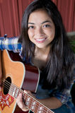 Teen playing guitar by barn Royalty Free Stock Image
