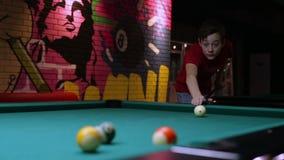 Teen playing pool billiard takes aim and hits ball stock video