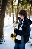 Teen playing saxophone in the snow Royalty Free Stock Photo