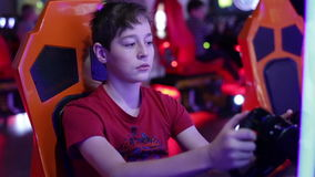 Teen playing on a slot machine simulator races. Teenager sits and spins the wheel on the slot machine simulator races stock video