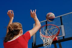 Teen plays basketball. And puts ball right in basket Royalty Free Stock Photos