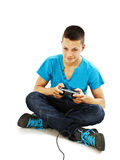 Teen plays on the joysticks sitting on the floor Royalty Free Stock Images