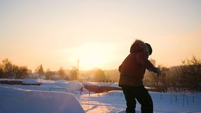 Teen plays on the Playground in winter. flips in the snow at sunset stock footage