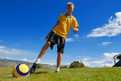 Teen plays soccer. On grass area Royalty Free Stock Image
