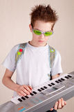 Teen plays on synthesizer. Indoor stock image
