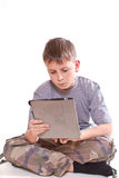 Teen plays on the tablet computer Stock Image