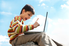 Teen pointing up while playing a laptop outside Royalty Free Stock Photo