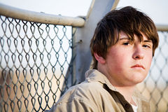 Teen portrait against fence. Teenager male with natural look sitting against fence looking into camera stock images