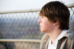 Teen portrait against fence. Teenager male portrait against a fence stock images