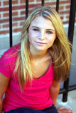 Teen pretty blond girl by fence Stock Photo