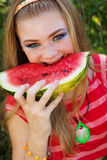 Teen pretty girl is eating watermelon over grass Stock Photos