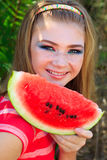 Teen pretty girl is eating watermelon over grass Royalty Free Stock Photo