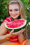 Teen pretty girl is eating watermelon over grass Stock Images