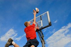 Teen puts ball in basket. Teens jumps high and puts ball in basket Stock Photography