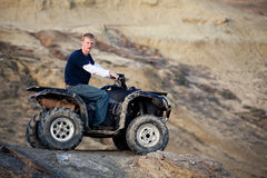 Teen on quad ATV in the hills. Teen riding a quad ATV - four wheeler in the hills Royalty Free Stock Image
