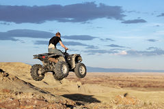 Teen on quad - four wheeler. Teen jumping on a quad - four wheeler 4x4 gets some air royalty free stock image