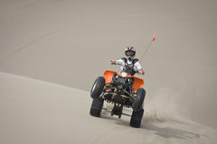 Teen quad rider wheelie in dunes royalty free stock photography