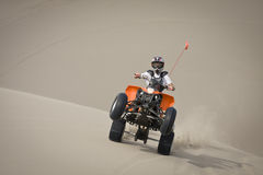 Teen quad rider wheelie in dunes Stock Photo