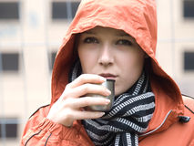 Teen with raincoat and drink Royalty Free Stock Image