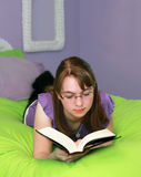 Teen Reading. A teenage girl reads while lounging on her bed Royalty Free Stock Photo
