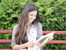 Teen Reading. Teen  Reading on a bench outdoor on a sunny day Stock Photos