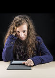 Teen reading on her e-reader. A teen girl reading on her e-reader on a table Stock Photo
