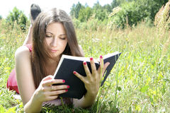 Teen reading in meadow. Attractive female teenager reading book in countryside field or meadow, summer scene Stock Image