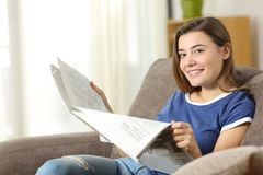 Teen reading a newspaper looking at camera at home. Teen reading a newspaper looking at camera sitting on a couch in the living room at home royalty free stock photo