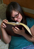 Teen reads Bible in her room Stock Photos