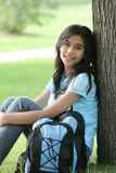 Teen Ready for High School. Beautiful teenage girl ready for her first day of high school. Sitting next to tree with backpack Stock Photos