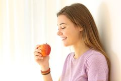 Teen ready to eat an apple indoors Royalty Free Stock Photography
