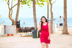 Teen in red dress walking on beach talking on phone Royalty Free Stock Photography