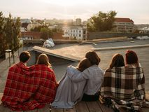 Teen relationship rooftop diverse couples dating. Teen relationship and dating. Back view of diverse couples in love sitting together on a rooftop and enjoying stock photo