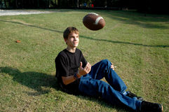 Teen Relaxation Football Style. A teenaged boy relaxes in the sunshine on a grassy knoll by tossing a football into the air Royalty Free Stock Photos