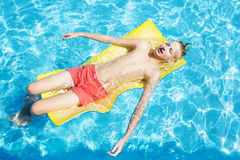 Teen relaxes in the pool Stock Photo
