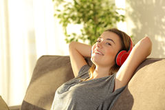 Teen relaxing and listening music at home. One teen listening music with headphones and looking at you sitting on a couch in the living room at home with a warm Stock Image