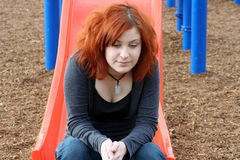 Teen Reminiscing At Playground Horizontal. Teen girl reminiscing at she sits on the end of a sliding board stock photo