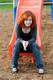 Teen Reminiscing At Playground Vertical. Teen girl reminiscing as she sits on the end of a playground sliding board stock photos